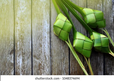 Ketupat (Rice Dumpling) On Wooden Background. Ketupat is a natural rice casing made from young coconut leaves for cooking rice during eid Mubarak, Fitri