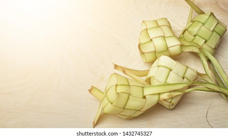 Ketupat (Rice Dumpling) On Wooden Background. Ketupat is a natural rice casing made from young coconut leaves for cooking rice during eid Mubarak,