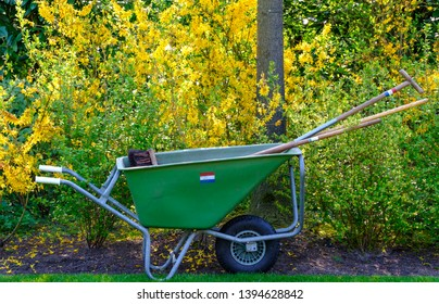 Keukenhof, Netherlands. April 2019. Green wheelbarrow with gardening tools inside, photographed at Keukenhof Gardens, Lisse, South Holland. Lisse is the centre of Holland's floriculture industry.