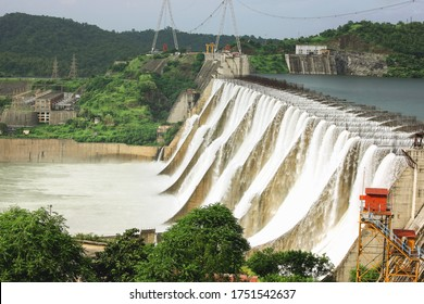 Kevadia ,10, September ,2010 : Side view of  Narmada River waters  overflowing  Sardar Sarovar Dam  with Hydro Electric Power Project and mountains in background at Kevadia, Gujarat, India, Asia