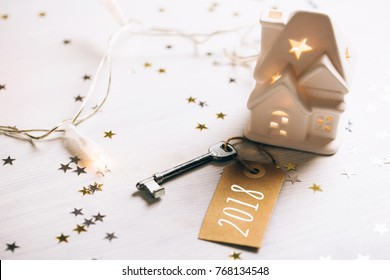 Key to 2018 year. Small toy white house with a roof, lights and key standing on wooden background with sparkles. New Year coming concept.