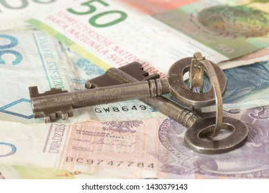 A key, and banknotes Polish zloty and Swiss francs