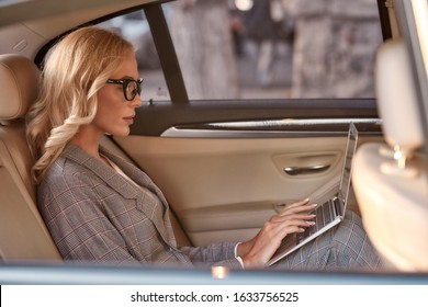 The key to being a successful business woman. Side view of beautiful and confident woman in full suit working on laptop while sitting in the car. Business concept. Work concept. Success
