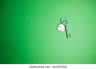 Key with key chain in form of house on a green background