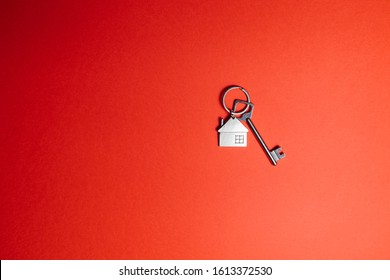 Key with key chain in form of house on a red background