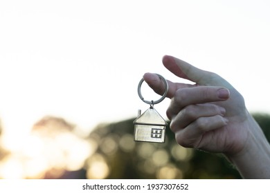 key chain in the form of a house in your hand of buying a home