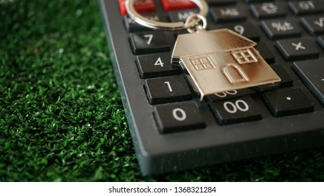Key chain in house shape and calculator. Real estate and house mortgage concept.
