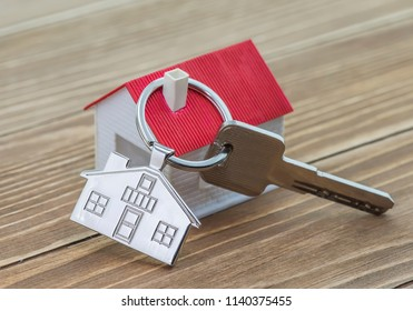key chain with house symbol and keys on wooden background,Real estate concept