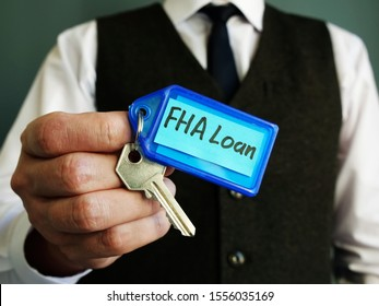 The key with FHA loan sign is in the hands of a man.