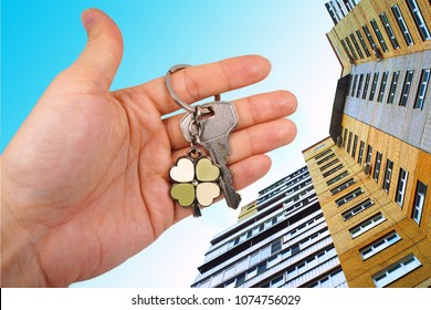 key in hand on the background of a multi-storey building