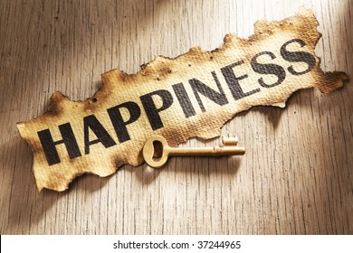Key to happiness concept using burnt paper with word happiness printed on it and golden key placed on its side