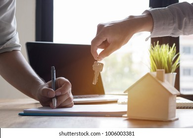 Key of home on hand of bank employeer  to sell house after approve loan and buyer signing in contract paper in office