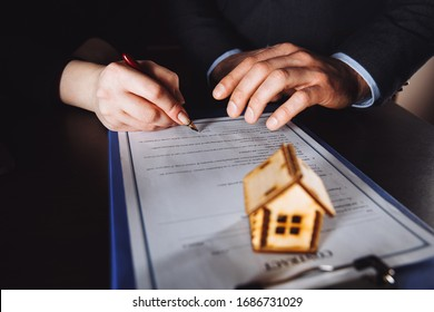 Key of home on hand of bank employeer to sell house after approve loan and buyer signing in contract paper in office.