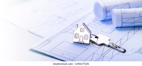Key with house as a key fob on blueprints in panorama format