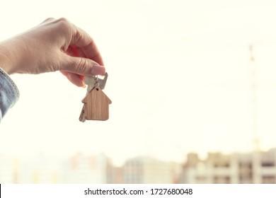 Llave con el llavero de la casa en el fondo con la construcción de nuevas casas de rascacielos. Compra de viviendas y concepto de bienes inmuebles