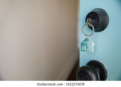 A Key with a House Keychain in the lock of a Front Door of a New Construction Home a Home