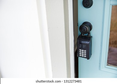 A Key with a House Keychain in the lock of a Front Door of a New Construction Home with Lock Box