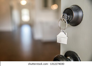 A Key with a House Keychain in the lock of a Front Door of a New Construction Hom