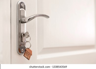 Key with house-shaped trinket in door lock, closeup. Space for text