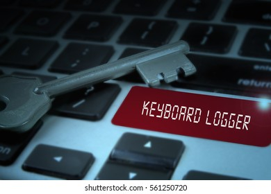 Key and keyboard with cyber security conceptual text. Low light.
