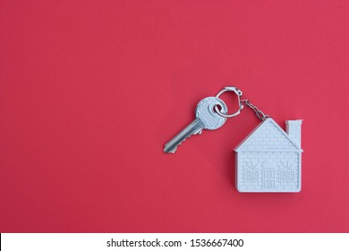 Key with a keychain in the form of a house on a red background. The concept of buying, selling, renting real estate, mortgages, your own home. Place for text