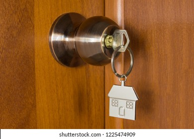 Key with keychain house in the door handle lock. Concept purchase sale of new housing, rent, mortgage, loan.