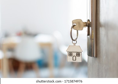Key with keychain in a house shape in the door keyhole. Buy new home concept. Real estate market. - Shutterstock ID 1715874976
