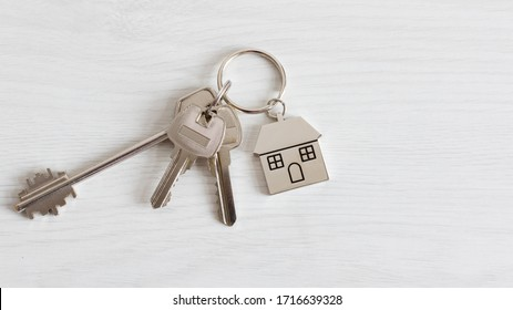 Key and keychain in a house shape on wooden background top view. Real estate concept. Copy space.