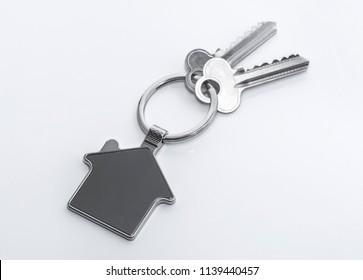 Key and keychain in the shape of a house isolated on white background.