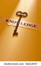 """A key laying on a piece of paper with the word """"knowledge"""" on it."""