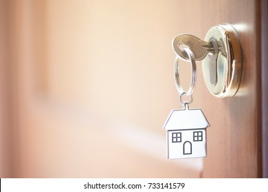 A key in a lock with house shape on it