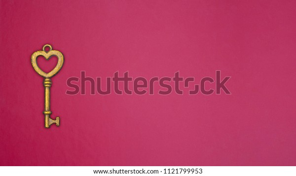 Key made from brass, heart shape, vintage style on red background.