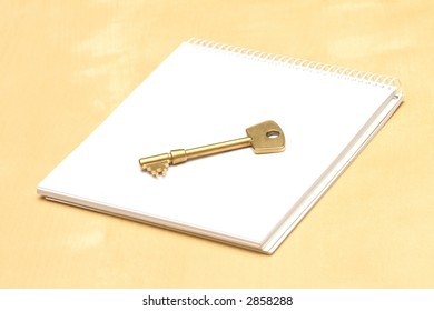 Key and notebook on a table