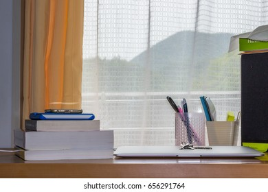 A Key on the Computer and There Are Some Books Nearby. Through the window can see the mountains stand far away.
