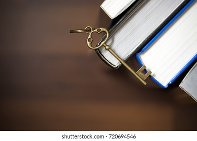 Key on hardback books over brown background, with copy space