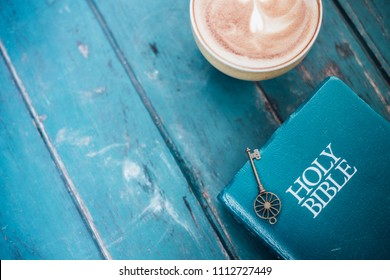 A key is on the holy bible with green wooden background.