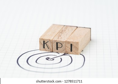 Key Performance Indicator, KPI concept, small wooden stamp combine the acronym KPI with hand draw arrow and target on white grid paper. Metric or measurement to achieve or success in business.