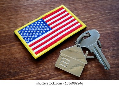 Key from property and USA flag. VA loan mortgage concept.