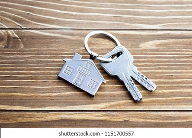 Key with silver house shaped pendant on wooden background