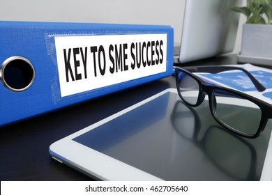 KEY TO SME SUCCESS  Small and medium-sized enterprises Office folder on Desktop on table with Office Supplies. ipad
