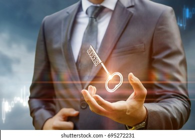 Key to success in businessman hand on background of the sky.