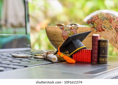 Key success in graduate study abroad program and open or expand world view concept : Graduation cap or hat, certificate or diploma, small text books on a laptop computer, coins in a half world globe.