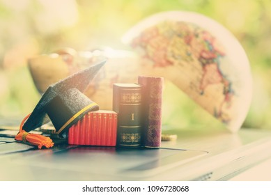 Key success in graduate study abroad program and open or expand world view concept : Graduation cap or hat, certificate or diploma, miniature text books on a laptop computer, a half sphere world globe