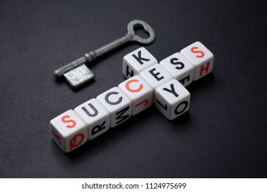 key to success, old vintage key on top and letter dice spelling key in vertical and success in horizontal, on black texture background for business idea concept, alphabet, text, cube, block, crossword