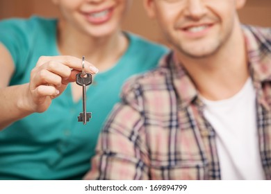 Key of their brand new house. Cropped image of cheerful young couple sitting close to each other and smiling while holding key from the house