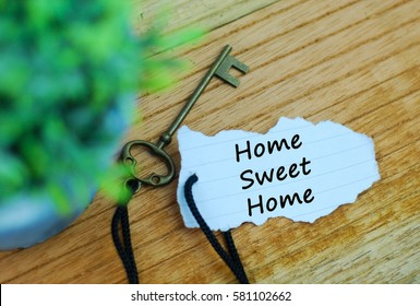 Key and torn paper with text home sweet home on wooden background