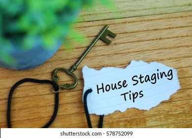 Key and torn paper with text house staging tips on wooden background