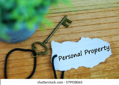Key and torn paper with text personal property on wooden background