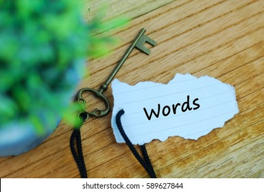 Key and torn paper with text words on wooden background. Keyword concept