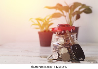 key, toy car and coins in bottle on wood background, concept in buying, selling, caring and loan car